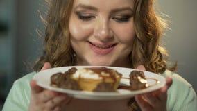 Έφηβος με τα πεινασμένα μάτια που θαυμάζει το σύνολο πιάτων των γλυκών κάτω από τη σάλτσα σοκολάτας απόθεμα βίντεο
