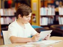Έφηβος με την ταμπλέτα στη βιβλιοθήκη Στοκ φωτογραφίες με δικαίωμα ελεύθερης χρήσης