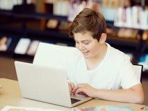 Έφηβος με την ταμπλέτα στη βιβλιοθήκη Στοκ Φωτογραφίες