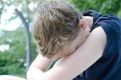 Έφηβος με το κεφάλι στα όπλα στοκ φωτογραφία με δικαίωμα ελεύθερης χρήσης