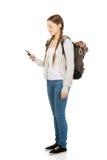 Έφηβος με το σακίδιο πλάτης που στέλνει sms Στοκ Φωτογραφία