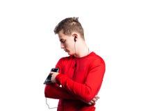 Έφηβος με το smartphone και τα ακουστικά Πυροβολισμός στούντιο, που απομονώνεται Στοκ φωτογραφία με δικαίωμα ελεύθερης χρήσης