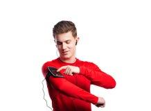 Έφηβος με το smartphone και τα ακουστικά Πυροβολισμός στούντιο, που απομονώνεται Στοκ εικόνα με δικαίωμα ελεύθερης χρήσης