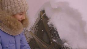 Έφηβος νέων κοριτσιών με το καθαρίζοντας καλυμμένο αυτοκίνητο χιόνι βουρτσών στο χειμερινό χώρο στάθμευσης φιλμ μικρού μήκους