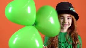Έφηβος νέων κοριτσιών που γιορτάζει την ημέρα Αγίου Πάτρικ ` s στα πορτοκαλιά μπαλόνια εκμετάλλευσης τοίχων απόθεμα βίντεο