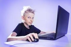 Έφηβος πίσω από έναν υπολογιστή στοκ εικόνα