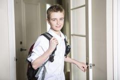 Έφηβος που έρχεται κατ' οίκον περνώντας μέσω της πόρτας στοκ εικόνες