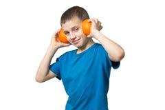 Έφηβος που ακούει τη μουσική μέσω των φρούτων ακουστικών στοκ φωτογραφία με δικαίωμα ελεύθερης χρήσης