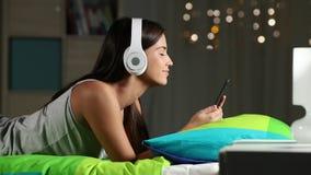 Έφηβος που ακούει τη μουσική με τα ακουστικά και το τηλέφωνο σε ένα κρεβάτι απόθεμα βίντεο
