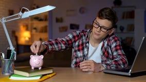 Έφηβος που βάζει τα χρήματα στο σηκωήσαστε στην πλάτη, freelancer, εργασία για τους σπουδαστές, πρώτος μισθός στοκ εικόνες