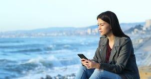Έφηβος που ελέγχει το τηλέφωνο και που εξετάζει τον ορίζοντα στην παραλία απόθεμα βίντεο