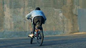 Έφηβος που κάνει τα τεχνάσματα σε ένα ποδήλατο BMX, σε αργή κίνηση απόθεμα βίντεο