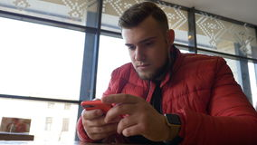 Έφηβος που κοιτάζει βιαστικά τα κοινωνικά μέσα στην έξυπνη τηλεφωνική οθόνη επαφής και που χρησιμοποιεί smartwatch φιλμ μικρού μήκους