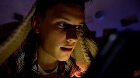 Έφηβος που κουβεντιάζει ή που παίζει στο smartphone που βρίσκεται κάτω από το κάλυμμα, εθισμός συσκευών στοκ εικόνα