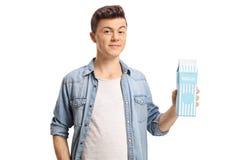Έφηβος που κρατά ένα χαρτοκιβώτιο γάλακτος στοκ εικόνες