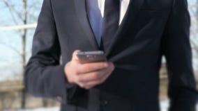 Έφηβος που κρατά το έξυπνο τηλέφωνο στην οδό το χειμώνα φιλμ μικρού μήκους