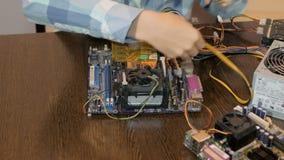 Έφηβος που μελετά τη συσκευή υπολογιστών Συνδέει με τα μέρη υπολογιστών απόθεμα βίντεο