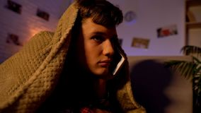 Έφηβος που μιλά στο τηλέφωνο μέχρι αργά - νύχτα, που βρίσκεται κάτω από το κάλυμμα, επικοινωνία στοκ εικόνες