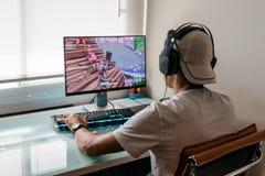 Έφηβος που παίζει το τηλεοπτικό παιχνίδι Fortnite στο PC στοκ φωτογραφίες με δικαίωμα ελεύθερης χρήσης