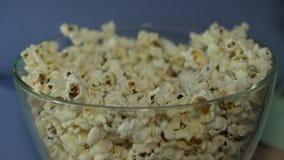 Έφηβος που τρώει popcorn γρήγορα από το κύπελλο στον κινηματογράφο απορροφημένο από τον κινηματογράφο, κινηματογράφηση σε πρώτο π απόθεμα βίντεο