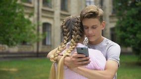 Έφηβος που χρησιμοποιεί το τηλέφωνο κυττάρων αγκαλιάζοντας το φίλο, που απορροφάται από τα κοινωνικά δίκτυα απόθεμα βίντεο