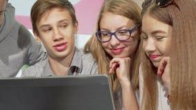Έφηβος που χρησιμοποιεί το lap-top στο σχολείο, που μελετά με τους συμμαθητές του απόθεμα βίντεο