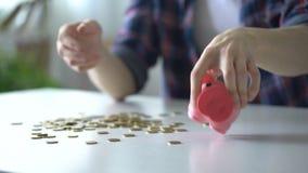 Έφηβος που χύνει έξω τα νομίσματα από τη piggy τράπεζα, όχι αρκετά χρήματα για την αγορά ονείρου φιλμ μικρού μήκους
