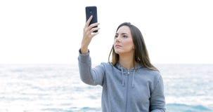 Έφηβος που ψάχνει την τηλεφωνική κάλυψη στην παραλία απόθεμα βίντεο