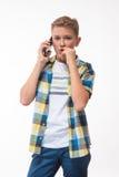 Έφηβος σε ένα πουκάμισο καρό με ένα τηλέφωνο στο χέρι του Στοκ εικόνες με δικαίωμα ελεύθερης χρήσης