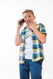 Έφηβος σε ένα πουκάμισο καρό με ένα τηλέφωνο στο χέρι του Στοκ Φωτογραφίες