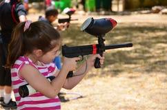 Έφηβος σε μια πρακτική στόχων με ένα πυροβόλο όπλο paintball Στοκ Φωτογραφίες