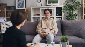 Έφηβος στον καθιερώνοντα τη μόδα ιματισμό που ακούει τη συνεδρίαση ψυχολόγων στην αρχή απόθεμα βίντεο