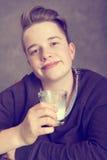 Έφηβος στο καφετί πόσιμο γάλα μπλουζών Στοκ Φωτογραφία