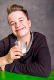 Έφηβος στο καφετί πόσιμο γάλα μπλουζών Στοκ φωτογραφία με δικαίωμα ελεύθερης χρήσης