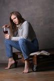 Έφηβος στο ποτήρι εκμετάλλευσης πουλόβερ του κρασιού Γκρίζα ανασκόπηση Στοκ Εικόνες