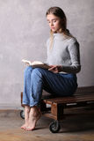 Έφηβος στο πουλόβερ που διαβάζει ένα βιβλίο Γκρίζα ανασκόπηση Στοκ εικόνα με δικαίωμα ελεύθερης χρήσης