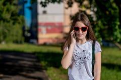 Έφηβος Brunette κοριτσιών Το καλοκαίρι στο πάρκο στο καθαρό αέρα Μιλά στο τηλέφωνο Ντυμένος στα γυαλιά ηλίου υπό μορφή Στοκ φωτογραφίες με δικαίωμα ελεύθερης χρήσης