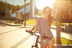 Έφηβος Hipster μόδας με το ποδήλατο στην πόλη στοκ εικόνα