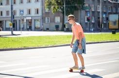 Έφηβος skateboard που διασχίζει τη διάβαση πεζών πόλεων Στοκ Εικόνα