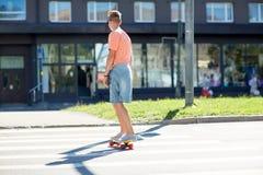 Έφηβος skateboard που διασχίζει τη διάβαση πεζών πόλεων Στοκ Φωτογραφία