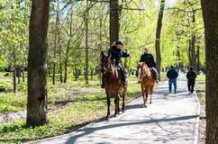 Έφιππη θηλυκό αστυνομία στο άλογο πίσω στο πάρκο πόλεων Στοκ φωτογραφία με δικαίωμα ελεύθερης χρήσης