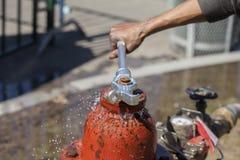 Έχον διαρροή ψεκάζοντας νερό στομίων υδροληψίας πυρκαγιάς που κλείνουν με το γαλλικό κλειδί Στοκ Εικόνες