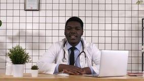 Έχω τις καλές ειδήσεις για σας Εύθυμος νέος αφρικανικός γιατρός που λέει τις καλές ειδήσεις στη κάμερα απόθεμα βίντεο