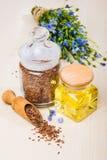 Έλαιο λιναρόσπορου, σπόροι λιναριού, και λουλούδια σε ένα ελαφρύ υπόβαθρο Στοκ Εικόνες