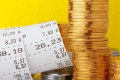 Έλεγχος παραλαβών εγγράφου καταλόγων μετρητών με τα νομίσματα Στοκ Φωτογραφία