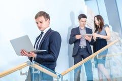 έλεγχος του ηλεκτρονι Νέος και επιτυχής επιχειρηματίας που στέκεται στο θόριο Στοκ Φωτογραφίες