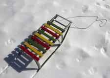 Έλκηθρα παιδιών ξύλου και μετάλλων χρώματος στο άσπρο χιόνι Στοκ Εικόνα