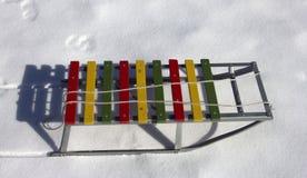 Έλκηθρα παιδιών ξύλου και μετάλλων χρώματος στο άσπρο χιόνι Στοκ φωτογραφία με δικαίωμα ελεύθερης χρήσης