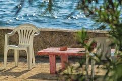 Έδρα στο ξύλινο πεζούλι με τον ξύλινο πίνακα πέρα από την μπλε θάλασσα κάτω από το μπλε ουρανό, έννοια διακοπών Στοκ εικόνα με δικαίωμα ελεύθερης χρήσης
