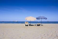 Έδρες και ομπρέλες σε μια όμορφη αμμώδη παραλία Στοκ εικόνες με δικαίωμα ελεύθερης χρήσης